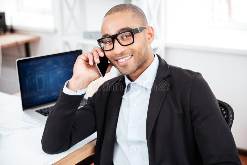 Giovane uomo d'affari che parla sul telefono cellulare e che esamina macchina fotografica fotografia stock
