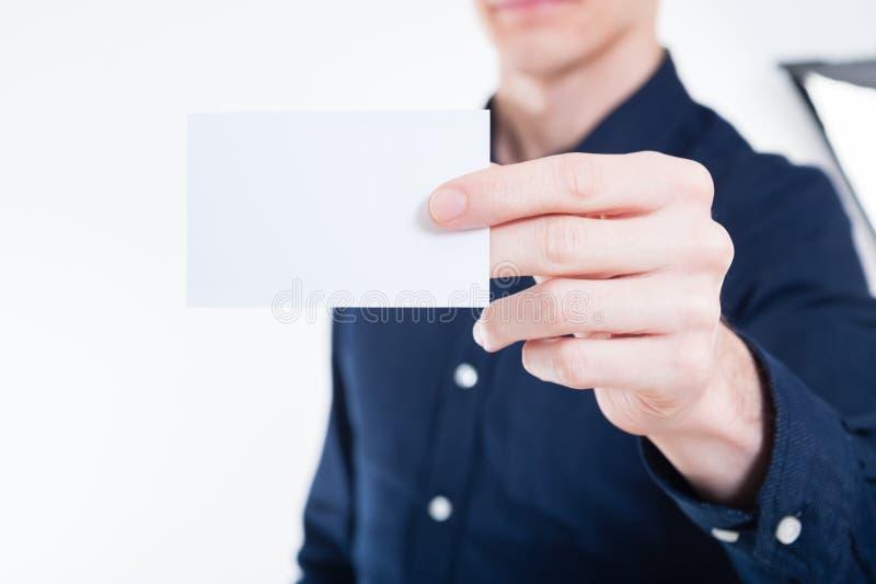 Giovane uomo d'affari che passa carta fotografia stock