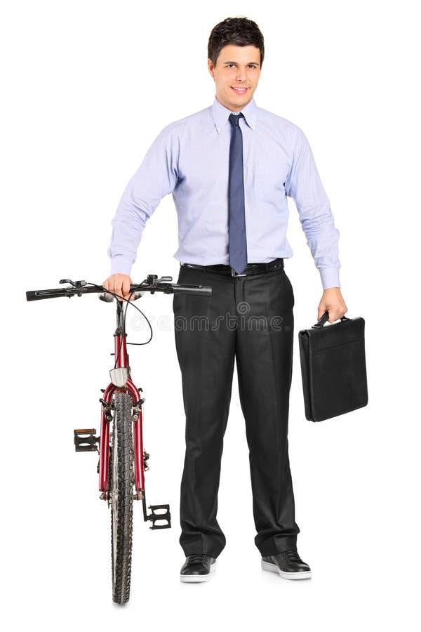 Giovane uomo d'affari che propone vicino ad una bicicletta fotografia stock libera da diritti