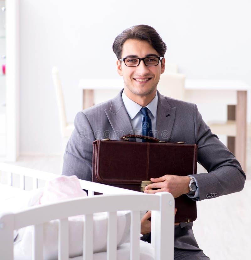 Giovane uomo d'affari che prova a lavorare dalla casa che si preoccupa dopo neonato fotografia stock libera da diritti