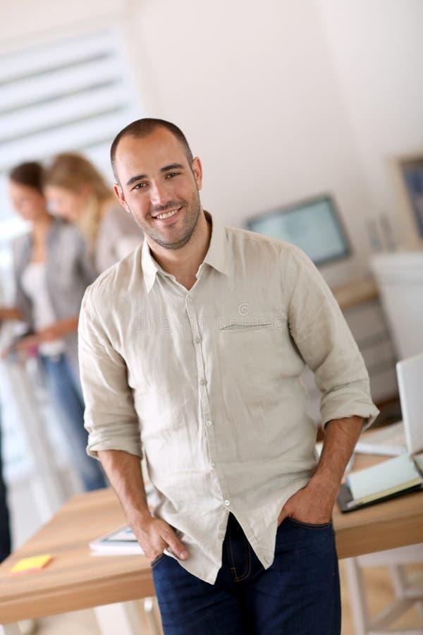 Giovane uomo d'affari che si appoggia la scrivania fotografie stock libere da diritti