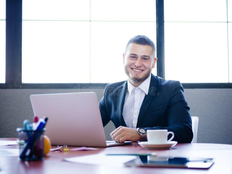 Giovane uomo d'affari che si siede al suo scrittorio con il computer portatile fotografie stock