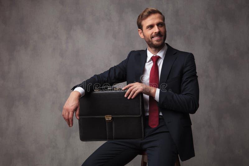 Giovane uomo d'affari che si siede con una valigia e gli sguardi al lato immagine stock libera da diritti