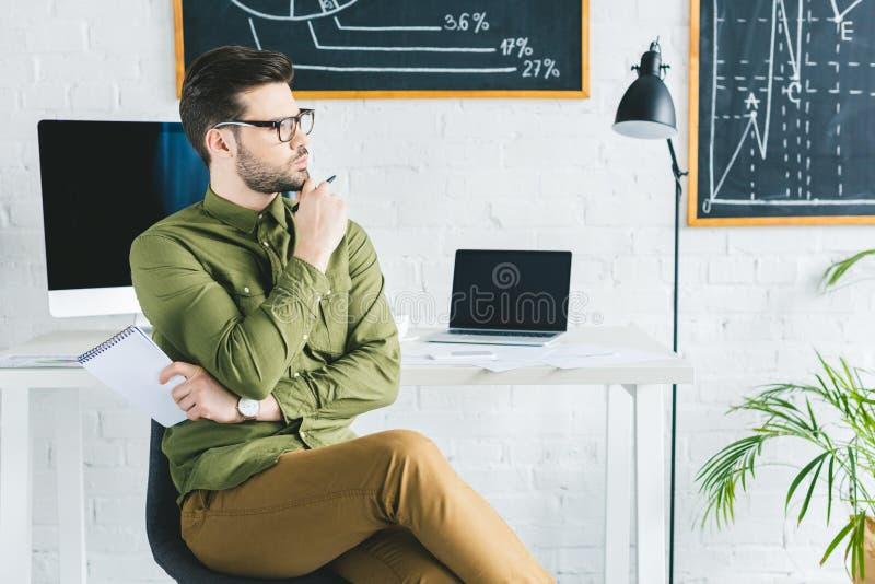 Giovane uomo d'affari che si siede dalla tavola con il computer immagine stock libera da diritti