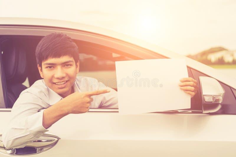 Giovane uomo d'affari che si siede nell'automobile moderna e che tiene spazio in bianco di fotografia stock libera da diritti