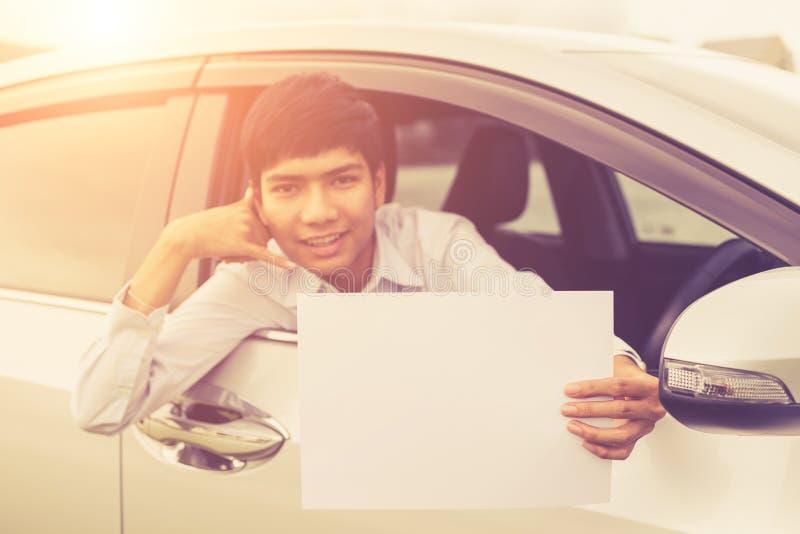 Giovane uomo d'affari che si siede nell'automobile moderna e che tiene spazio in bianco di fotografie stock