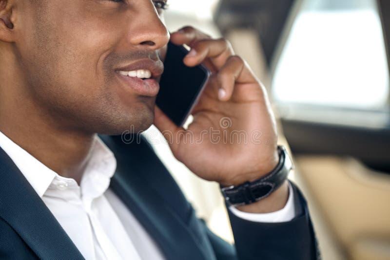 Giovane uomo d'affari che si siede nell'automobile che parla sul primo piano dello smartphone allegro fotografie stock