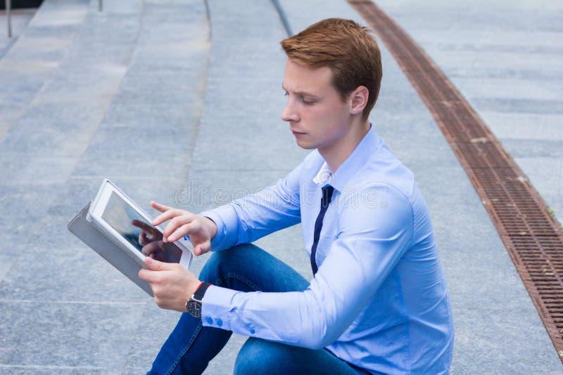 Giovane uomo d'affari che si siedono nella via vicino al centro di affari e gli impianti sulla compressa fotografia stock libera da diritti