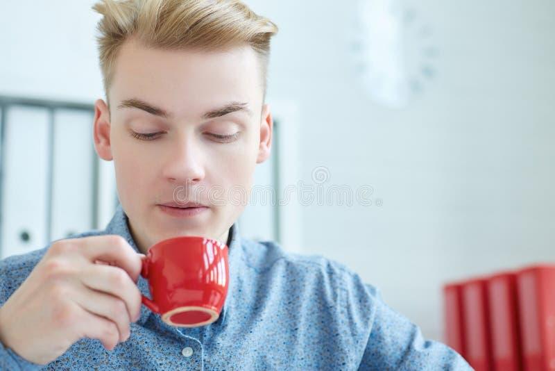 Giovane uomo d'affari che soffia una tazza di caffè calda in ufficio Breve pausa sul lavoro immagini stock