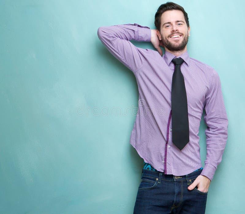 Giovane uomo d'affari che sorride contro il fondo blu fotografia stock