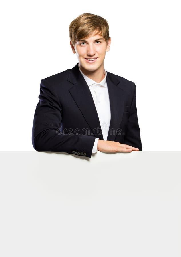 Giovane uomo d'affari che sta con una lavagna del balnk, isolata immagine stock libera da diritti