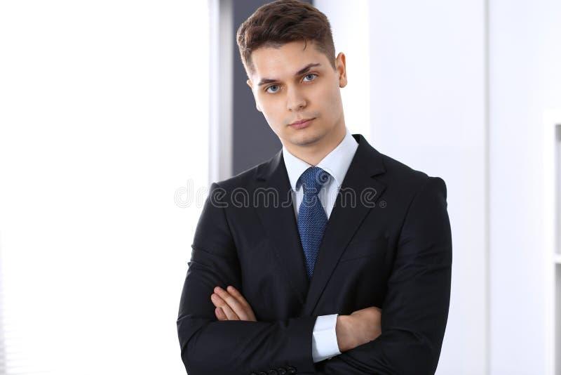 Giovane uomo d'affari che sta nell'ufficio con le armi attraversate Concetto di affari fotografie stock