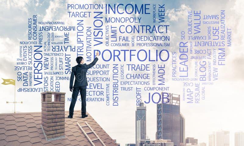 Giovane uomo d'affari che sta sul tetto della casa e che scrive direzione fotografie stock