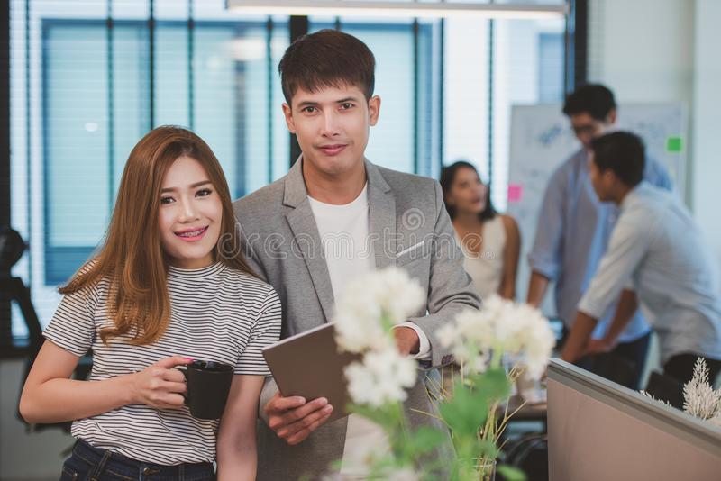 Giovane uomo d'affari che tiene compressa digitale con i colleghi femminili nel fondo fotografia stock