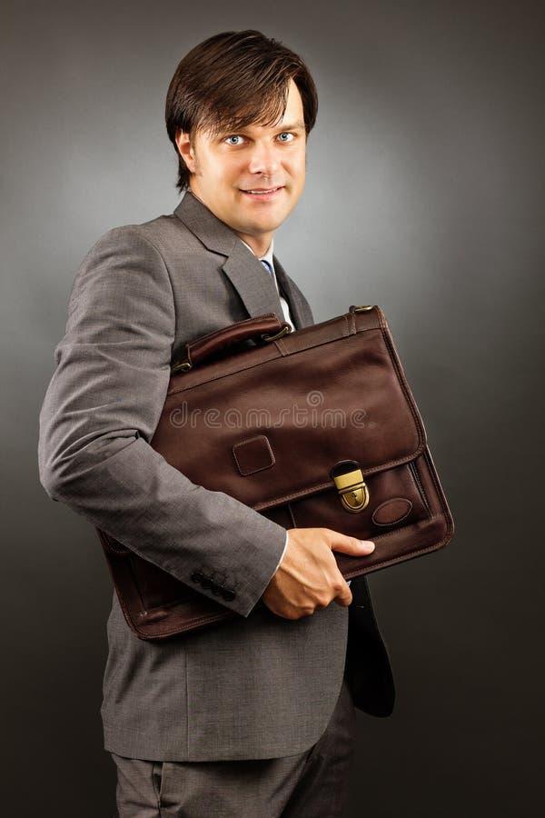 Giovane uomo d'affari che tiene la sua cartella fotografia stock libera da diritti