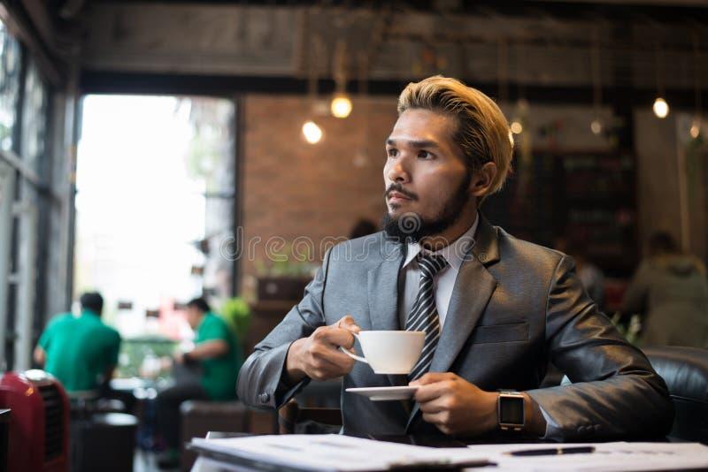 Giovane uomo d'affari che tiene tazza di caffè mentre lavorando al computer portatile immagine stock