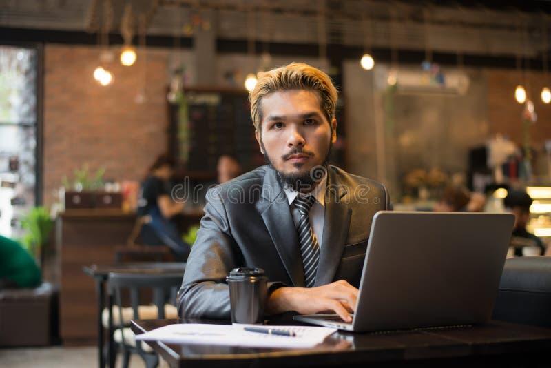 Giovane uomo d'affari che tiene tazza di caffè mentre lavorando al computer portatile immagini stock