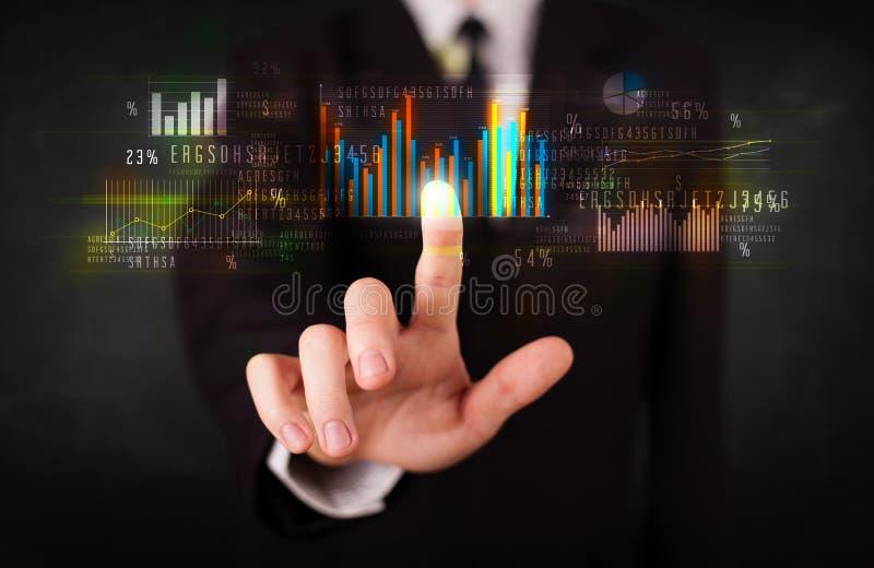 Giovane uomo d'affari che tocca i grafici variopinti ed i diagrammi immagine stock libera da diritti