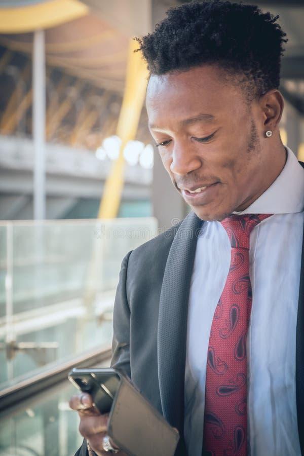 Giovane uomo d'affari che va all'aeroporto che guarda il suo telefono e immagini stock libere da diritti