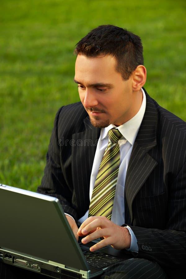 Giovane uomo d'affari con il computer portatile immagine stock libera da diritti