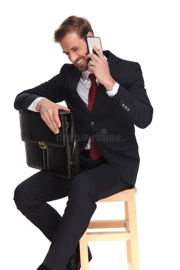 Giovane uomo d'affari con la valigia che si siede e che ride sul fon fotografia stock libera da diritti