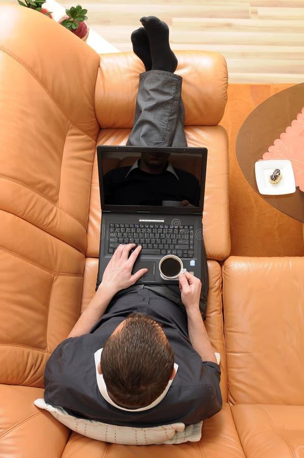 Giovane uomo d'affari con un computer portatile sulla bevanda dello strato fotografia stock libera da diritti
