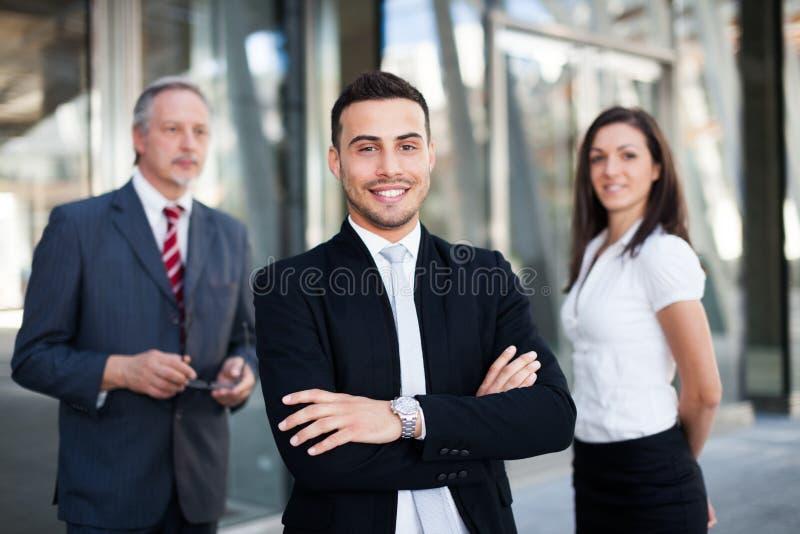 Giovane uomo d'affari davanti ad un gruppo di gente di affari all'aperto immagine stock libera da diritti