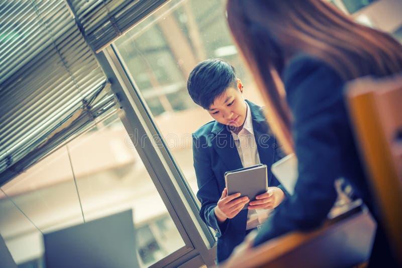 Giovane uomo d'affari dell'Asia in ufficio facendo uso del computer della compressa fotografie stock libere da diritti