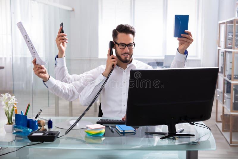 Giovane uomo d'affari Doing Multitasking Work fotografia stock libera da diritti