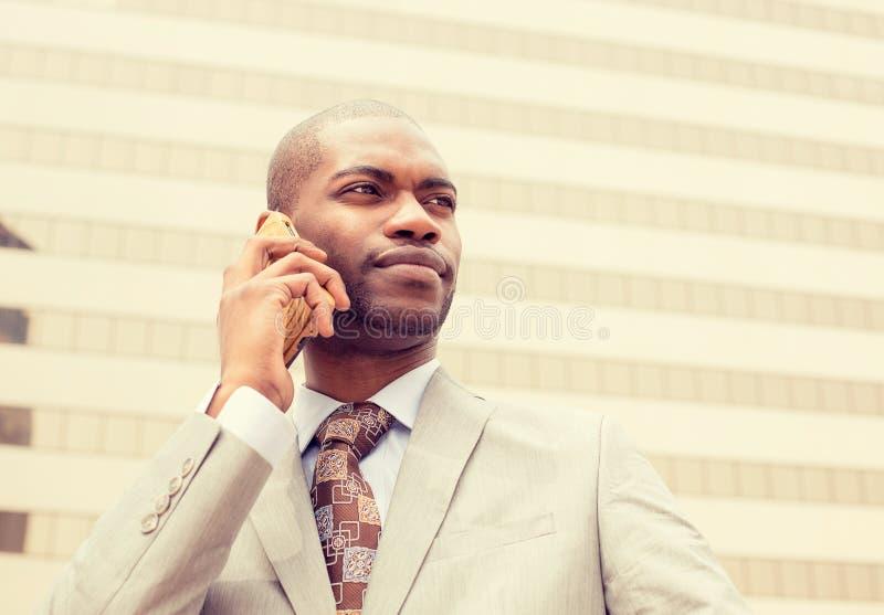 Giovane uomo d'affari felice bello che parla sul telefono cellulare immagine stock