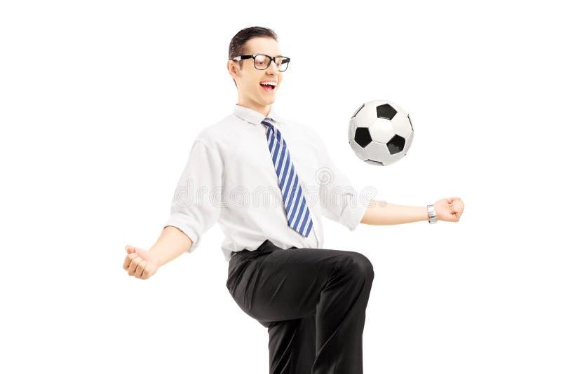Giovane uomo d'affari felice che gioca con un pallone da calcio fotografia stock libera da diritti