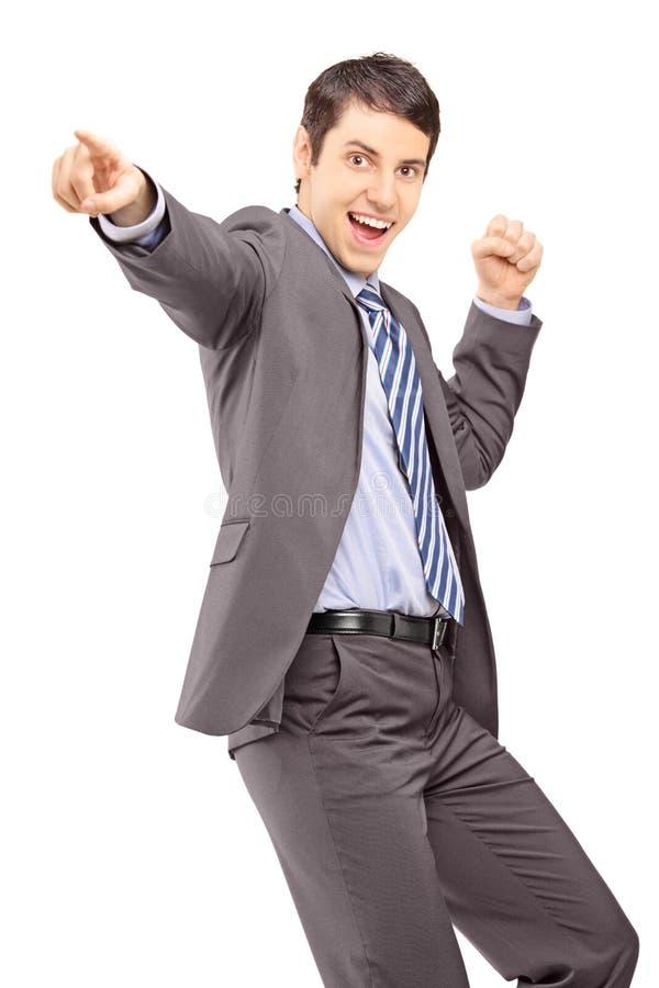 Giovane uomo d'affari felice che indica con il suo dito e che gesturing h immagini stock libere da diritti
