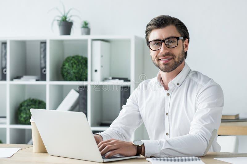 giovane uomo d'affari felice che lavora con il computer portatile all'ufficio moderno ed allo sguardo immagine stock
