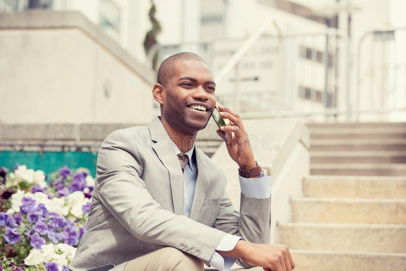 Giovane uomo d'affari felice che parla sul telefono cellulare che si siede all'aperto fotografia stock