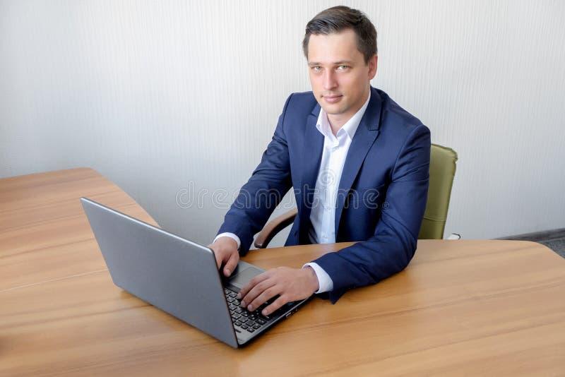 Giovane uomo d'affari felice facendo uso del computer portatile alla sua scrivania immagini stock libere da diritti