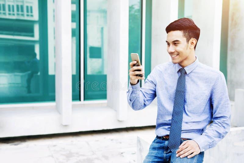 Giovane uomo d'affari felice Smilingwhile che usando Smartphone all'esterno fotografie stock
