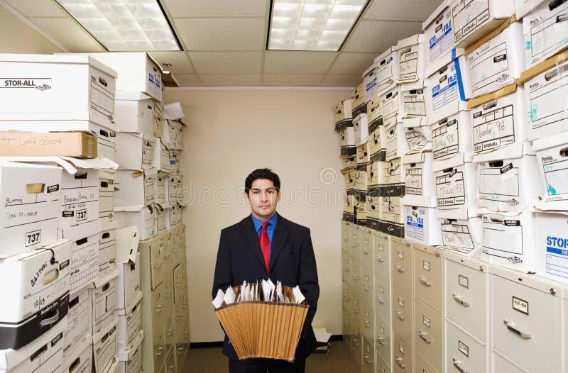 Giovane uomo d'affari fra gli archivi fotografie stock