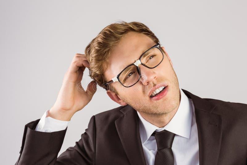 Giovane uomo d'affari geeky che graffia il suo capo immagine stock libera da diritti