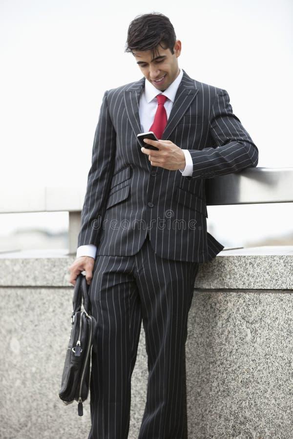Giovane uomo d'affari indiano che manda un sms tramite il telefono cellulare mentre tenendo la borsa del computer portatile al par fotografia stock libera da diritti