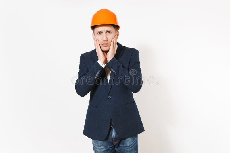 Giovane uomo d'affari interessato bello in vestito scuro, casco arancio della costruzione protettiva che tiene le mani vicino al  immagine stock libera da diritti