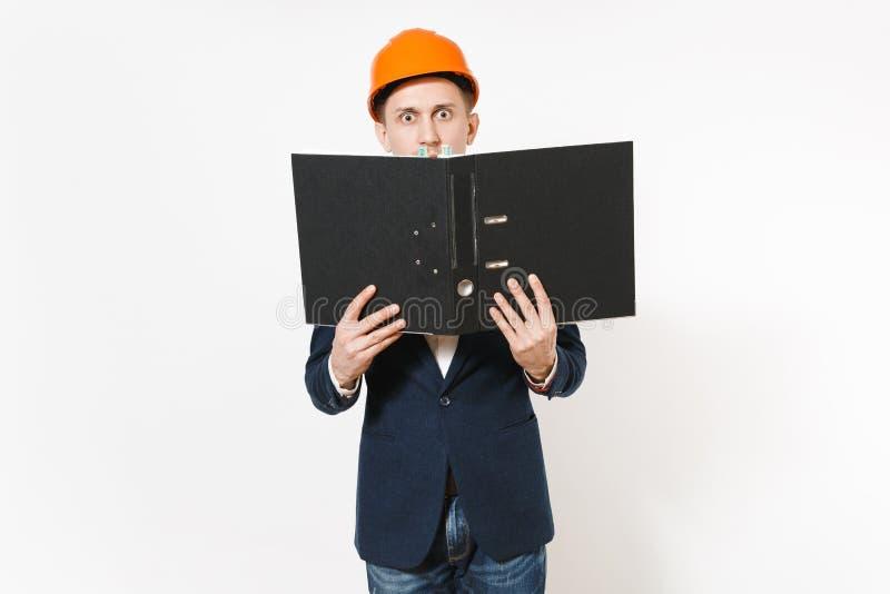 Giovane uomo d'affari interessato in vestito scuro, elmetto protettivo protettivo che tiene cartella nera per il documento di car fotografia stock libera da diritti