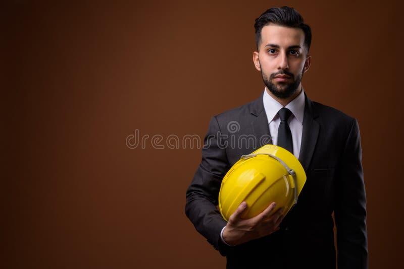 Giovane uomo d'affari iraniano barbuto bello con l'elmetto protettivo contro immagini stock libere da diritti