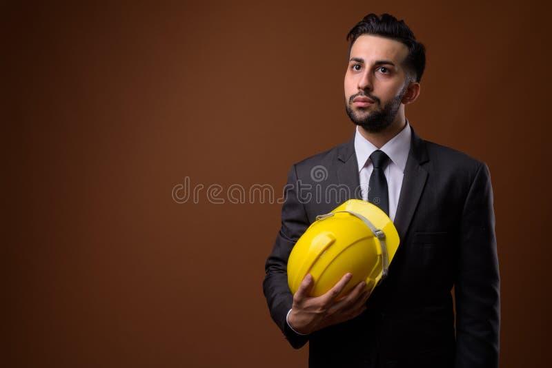 Giovane uomo d'affari iraniano barbuto bello con l'elmetto protettivo contro fotografie stock