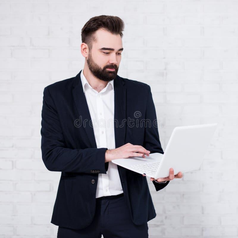 Giovane uomo d'affari ispanico che per mezzo del computer portatile sopra il muro di mattoni bianco immagini stock libere da diritti