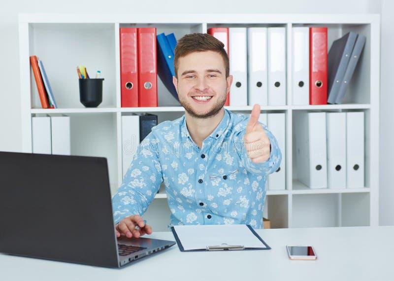 Giovane uomo d'affari maschio che mostra segno GIUSTO con il pollice su che si siede all'ufficio fotografie stock