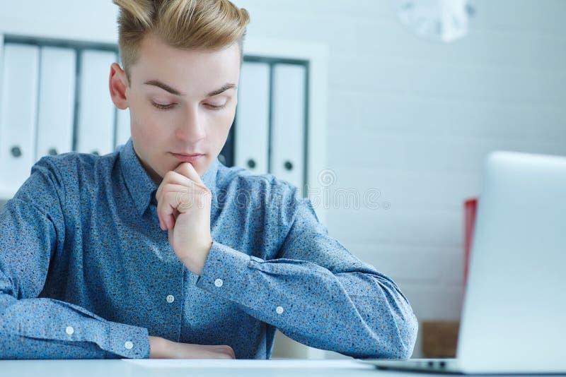 Giovane uomo d'affari maschio che prende le note sul computer portatile, lavorando con il grafico di dati, sedentesi nell'ufficio fotografie stock libere da diritti