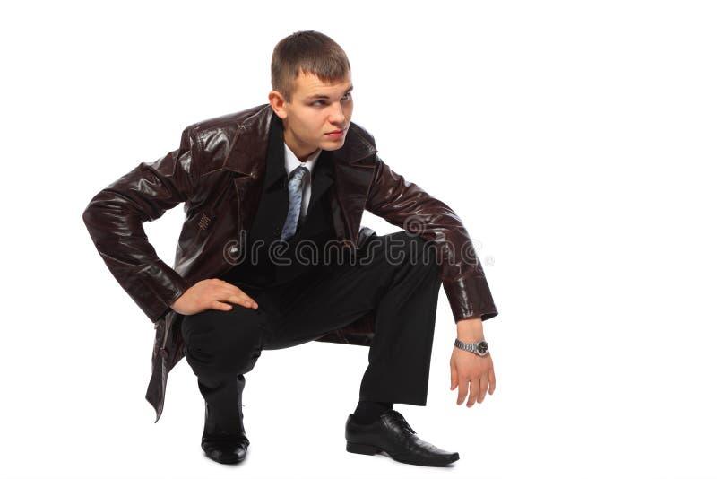Giovane uomo d'affari nelle posizioni accoccolate del rivestimento di cuoio fotografia stock