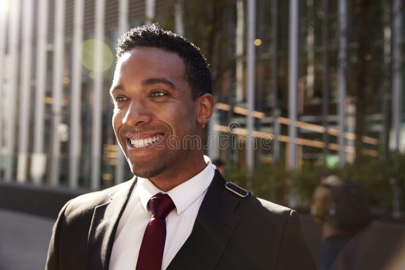Giovane uomo d'affari nero che indossa condizione nera sulla via che sorride, fine del vestito su con il chiarore della lente fotografia stock