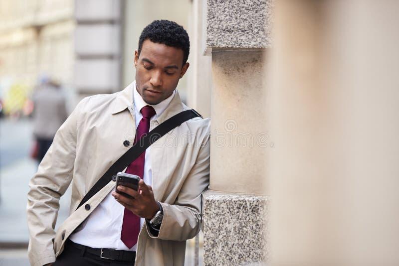 Giovane uomo d'affari nero che si appoggia una parete nella via a Londra facendo uso dello smartphone, fuoco selettivo fotografia stock