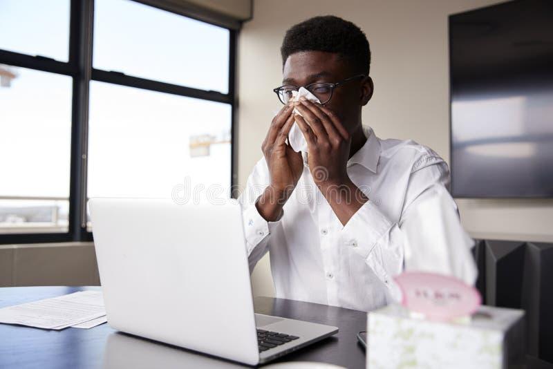 Giovane uomo d'affari nero che si siede ad una scrivania che soffia il suo naso in un tessuto immagini stock libere da diritti